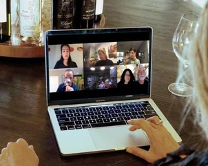 A Virtual Guided Wine Tasting with attendees in a Zoom meeting grid on a laptop screen with wine bottles in the background.