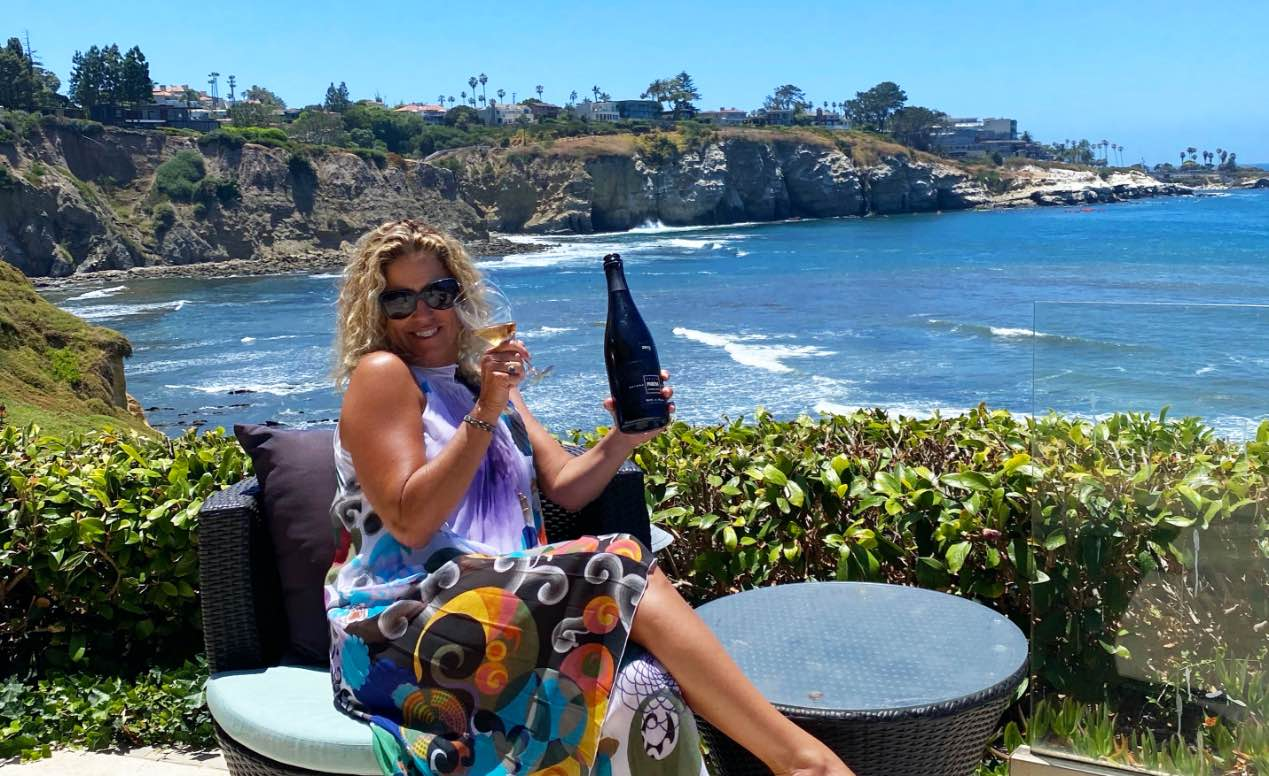 Nina Snow, owner of DOCG Imports, holding a bottle of Italian wine with La Jolla Cove in the background.