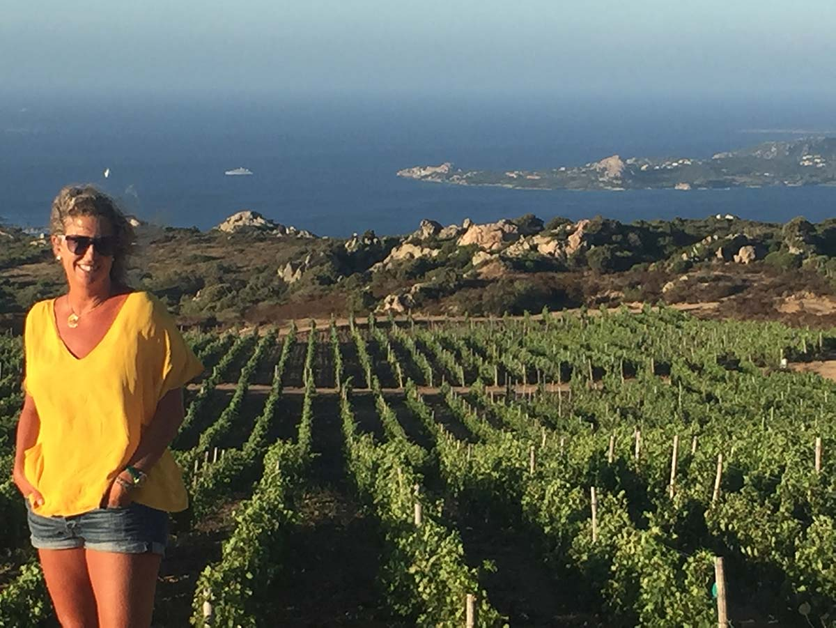 Nina Snow, Owner of DOCG Imports, standing in a Sardinian vineyard overlooking the Mediterranean Sea
