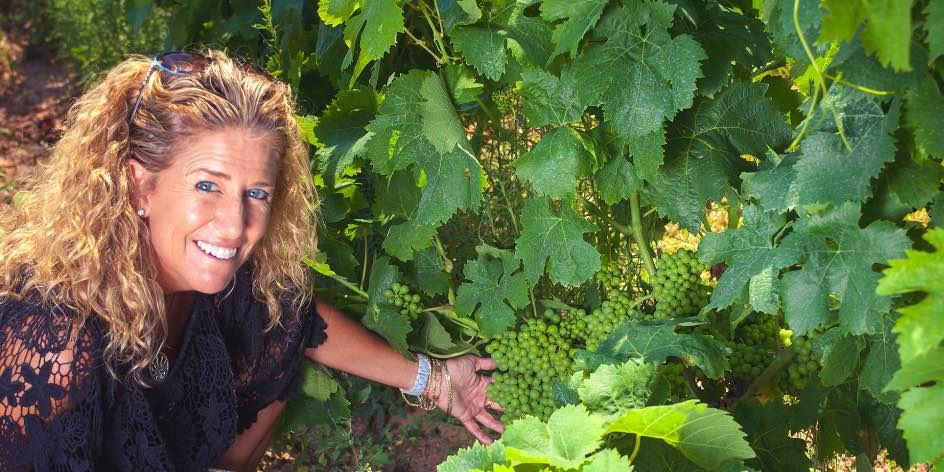 Nina Snow in Cantina Giba vineyard showing how low the fruit grows on the vines